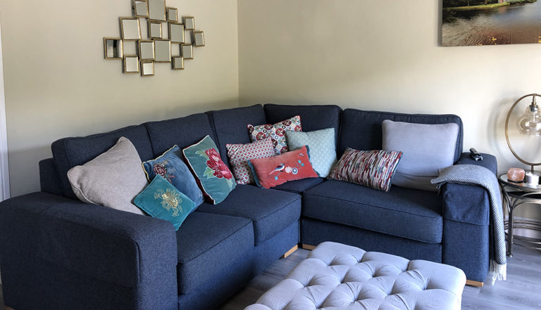 blue navy corner sofa and grey storage footstool in a living room