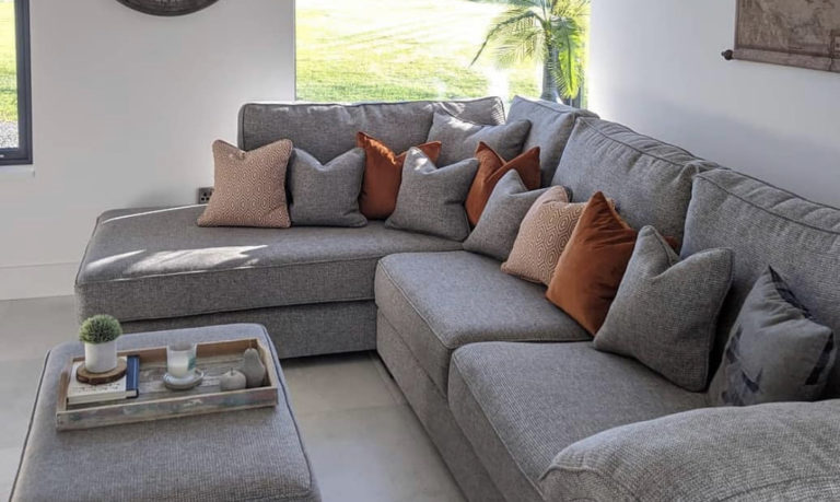 grey corner sofa, and grey footstool in a living room