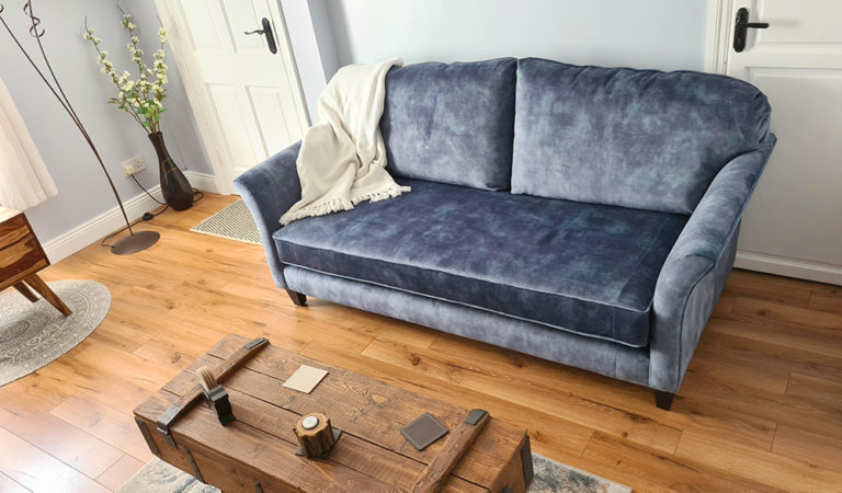 blue navy velvet sofa in a living room