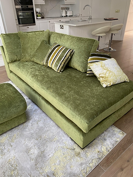 green velvet chaise sofa in a living room
